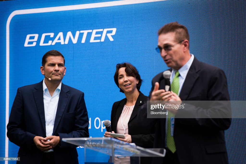Marc Llistosella, chief executive officer of MitsubishiFusoTruck and Bus Corp., left, and Jecka Glasman, chief executive officer of Mitsubishi Fuso Truck of America Inc., center, listen during the eCanter truck launch event in New York, U.S., on Thursday, Sept. 14, 2017. The Daimler AG unit unveiled the new Fuso eCanter, an electric light-duty truck produced under its Mitsubishi Fuso brand. The latest version has a range of 60 to 80 miles (97 to 129 kilometers) between charges, depending on body, load and usage. Photographer: Mark Kauzlarich/Bloomberg via Getty Images