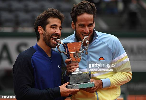 Marc Lopez and Feliciano Lopez of Spain celebrate with the trophy following their victory during the Men's Doubles final match against Mike Bryan and...