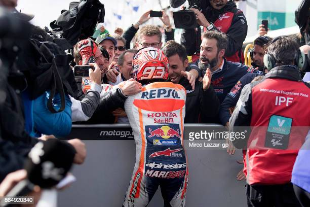 Marc Marquez of Spain and Repsol Honda Team celebrates victory with team under the podium at the end of the MotoGP race during the 2017 MotoGP of...