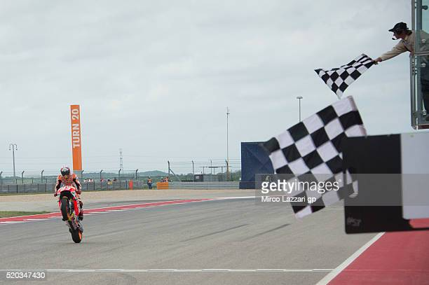 Marc Marquez of Spain and Repsol Honda Team cuts the finish lane and celebrates the victory at the end of the MotoGP race during the MotoGp Red Bull...
