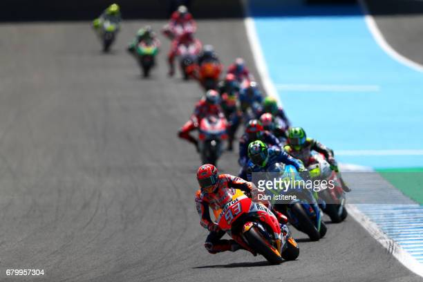 Marc Marquez of Spain and the Repsol Honda Team rides ahaead of Andrea Iannone of Italy and Team SUZUKI ECSTAR during the MotoGP of Spain at Circuito...