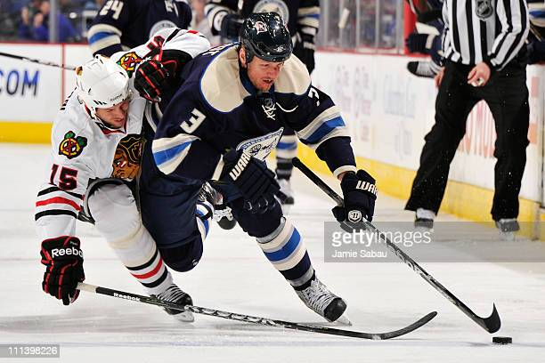 Marc Methot of the Columbus Blue Jackets and Fernando Pisani of the Chicago Blackhawks battle for a control of the puck during the third period on...
