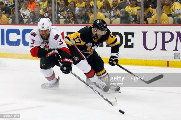 Marc Methot of the Ottawa Senators attempts to steer the puck away from Bryan Rust of the Pittsburgh Penguins in Game Five of the Eastern Conference...