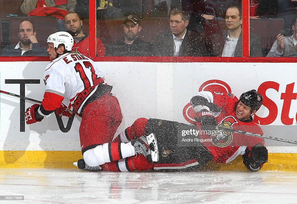 Marc Methot #3 of the Ottawa Senators crashes into the boards with Eric Staal #12 of the Carolina Hurricanes on February 7, 2013 at Scotiabank Place in Ottawa, Ontario, Canada.
