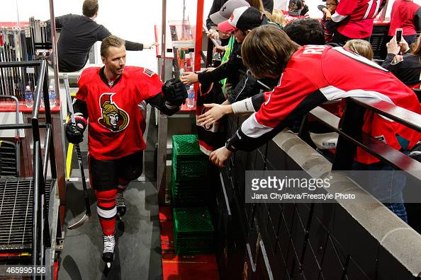 Marc Methot of the Ottawa Senators fist bumps fans as he steps off the ice during warmups prior to an NHL game against the Boston Bruins at Canadian...