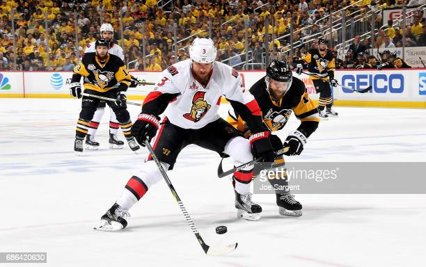 Marc Methot of the Ottawa Senators handles the puck against Bryan Rust of the Pittsburgh Penguins in Game Five of the Eastern Conference Final during...