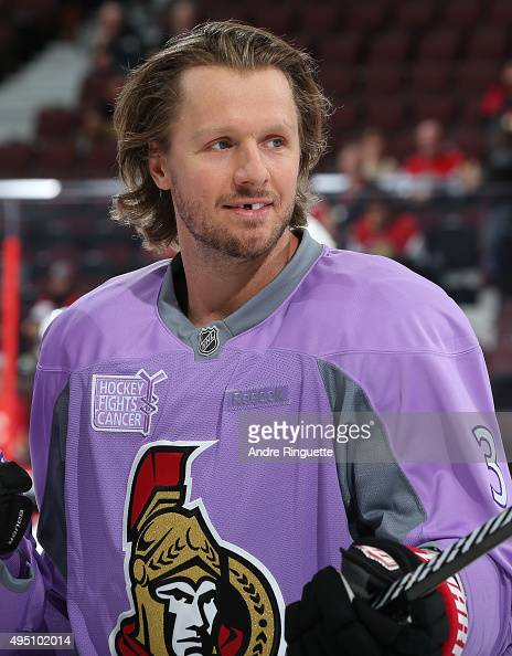 Marc Methot of the Ottawa Senators skates wearing a lavender jersey during warmup on Hockey Fights Cancer night prior to a game against the Calgary...