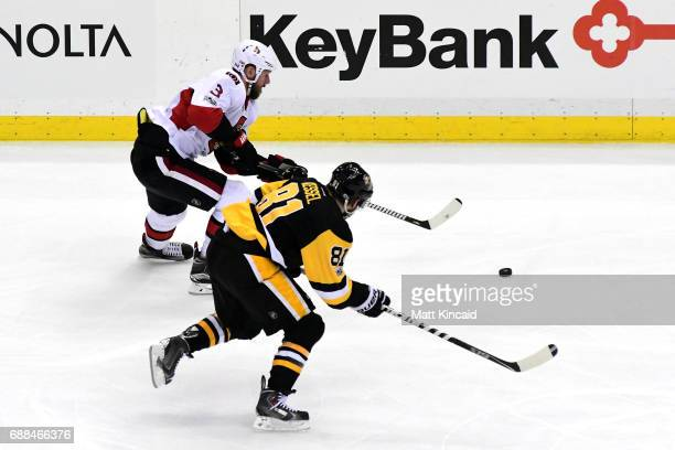 Marc Methot of the Ottawa Senators skates with the puck against Phil Kessel of the Pittsburgh Penguins during the first period in Game Seven of the...