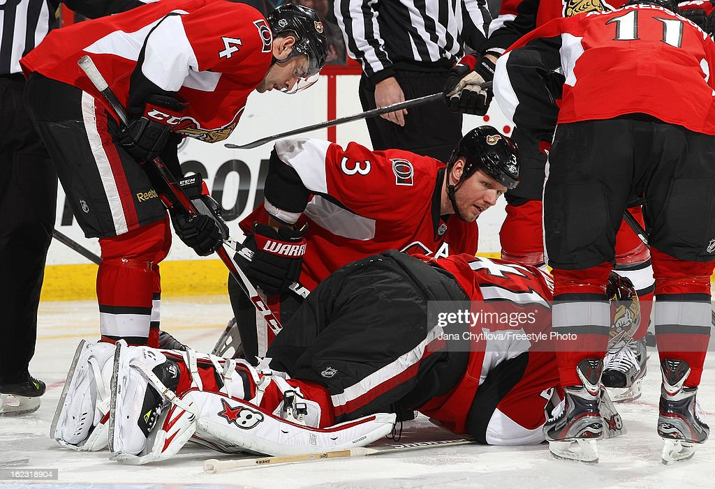 Marc Methot #3 of the Ottawa Senators talks to Craig Anderson #41 of the Ottawa Senators as he lies on the ice after being injured in a play, during an NHL game against the New York Rangers, at Scotiabank Place on February 21, 2013 in Ottawa, Ontario, Canada.