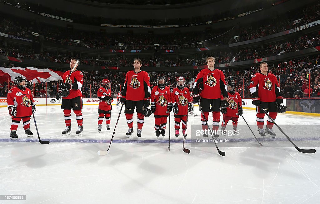 Marc Methot #3, Zack Smith #15, Colin Greening #14 and Mark Borowiecki #74 of the Ottawa Senators stand with minor hockey players during the singing of the national anthems prior to a game against the Florida Panthers at Canadian Tire Centre to kick off Minor Hockey Week on November 9, 2013 in Ottawa, Ontario, Canada.