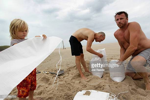 Marc Murphy John Wellmann and Callen Murphy fill sandbags on the beach as they prepare their home against Hurricane Irene on August 27 2011 in Water...