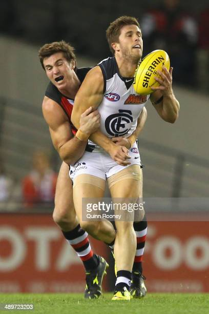 Marc Murphy of the Blues handballs whilst being tackled by Lenny Hayes of the Saints during the round eight AFL match between the St Kilda Saints and...