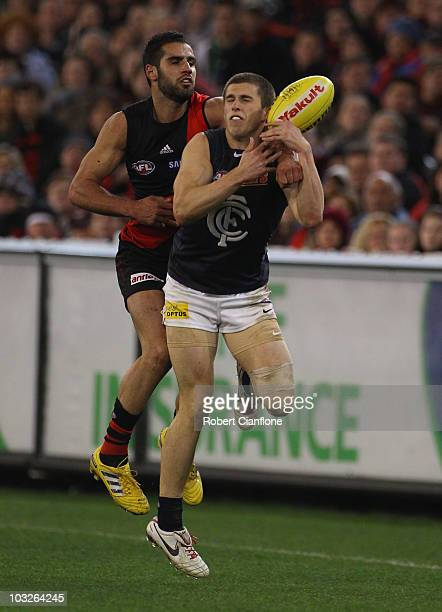 Marc Murphy of the Blues has the ball spoiled by Bachar Houli of the Blues during the round 19 AFL match between the Essendon Bombers and the Carlton...