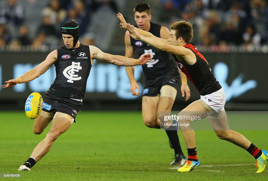 Marc Murphy of the Blues kicks the ball away from Zach Merrett of the Bombers during the round six AFL match between the Carlton Blues and the Essendon Bombers at Melbourne Cricket Ground on May 1, 2016 in Melbourne, Australia.