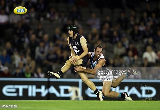 Marc Murphy of the Blues kicks whilst being tackled by Matthew Broadbent of Port Adelaide during the round eight AFL match between the Carlton Blues...