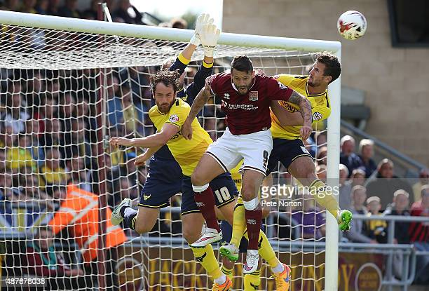 Marc Richards of Northampton Town challenges for the ball with Danny Hylton Jake Wright and Sam Slocombe of Oxford United during the Sky Bet League...