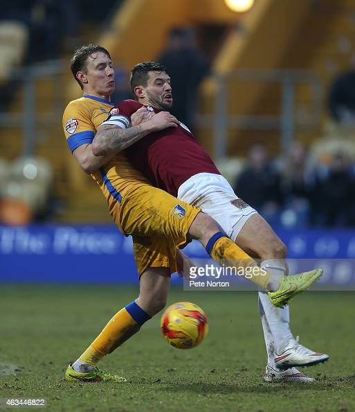 Marc Richards of Northampton Town contests the ball with Martin Riley of Mansfield Town during the Sky Bet League Two match between Mansfield Town...