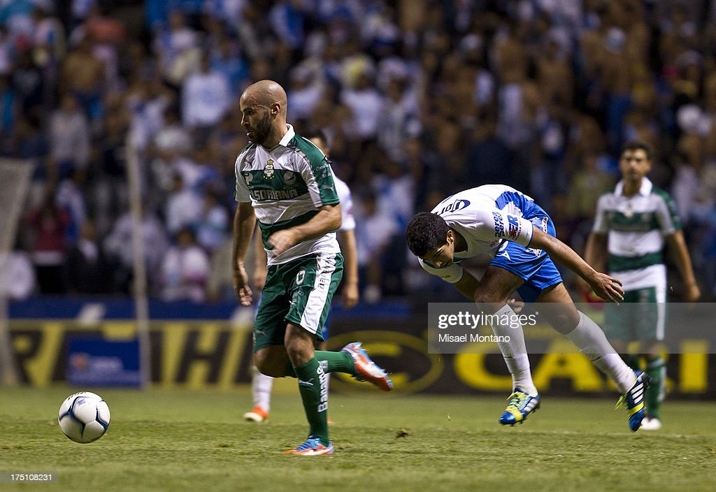 Marc Rosas of Santos competes for the ball with Luis Noriega of Puebla during a match between Puebla and Santos as part of the Torneo de Apertura 2013 Liga MX Championship at Cuauhtemoc Stadium, on July 31, 2013 in Puebla, Mexico.