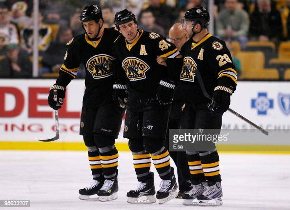 Marc Savard of the Boston Bruins is helped off the ice by teammates Mark Recchi and Marco Sturm in the first period against the Chicago Blackhawks on...