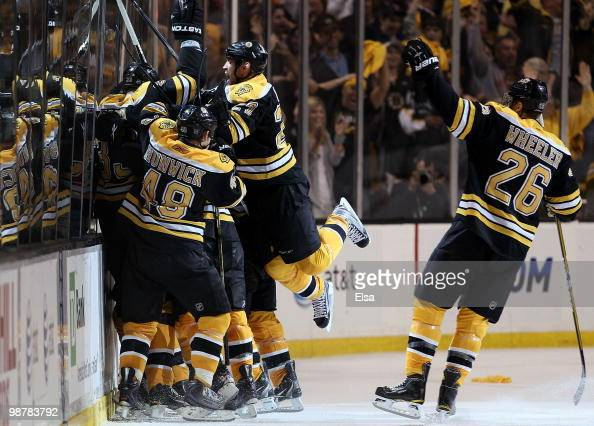Marc Savard of the Boston Bruins is swarmed by teamamtes Matt HunwickSteve Begin and Blake Wheeler after Savard scored the game winning goal in...