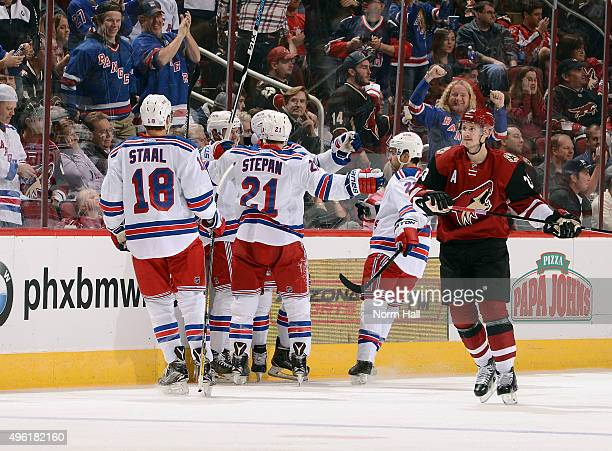 Marc Staal and Derek Stepan of the New York Rangers join in the celebration of teammates Chris Kreider's goal as Oliver EkmanLarsson of the Arizona...