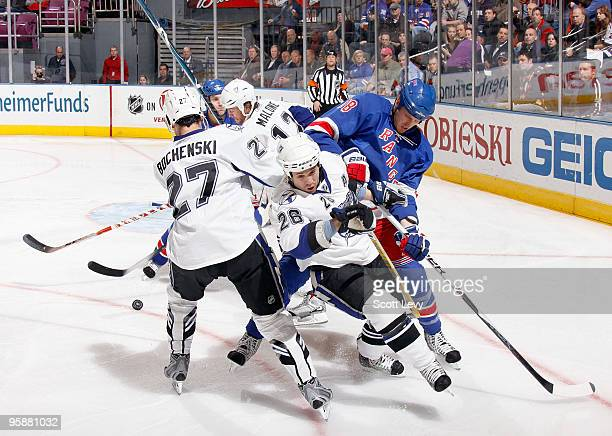 Marc Staal and Michael Del Zotto of the New York Rangers battle for the puck against Ryan Malone Brandon Bochenski and Martin StLouis of the Tampa...