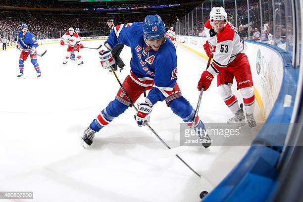 Marc Staal of the New York Rangers and Jeff Skinner of the Carolina Hurricanes battle for the puck in the corner at Madison Square Garden on December...