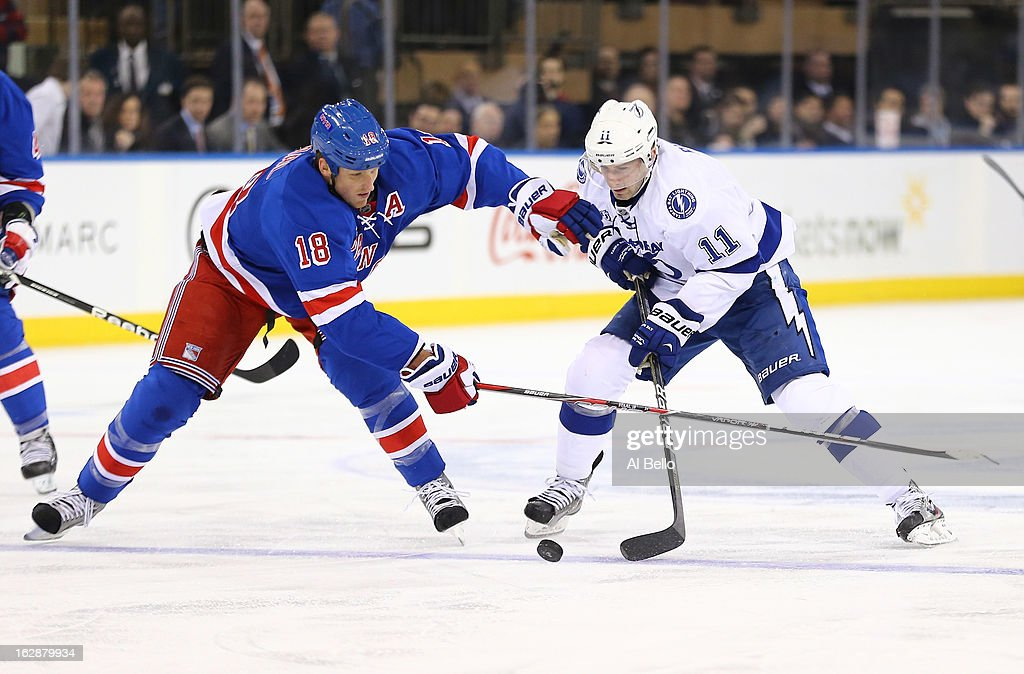 <a gi-track='captionPersonalityLinkClicked' href=/galleries/search?phrase=Marc+Staal&family=editorial&specificpeople=3809026 ng-click='$event.stopPropagation()'>Marc Staal</a> #18 of the New York Rangers and <a gi-track='captionPersonalityLinkClicked' href=/galleries/search?phrase=Tom+Pyatt&family=editorial&specificpeople=2079036 ng-click='$event.stopPropagation()'>Tom Pyatt</a> #11 of the Tampa Bay Lightning fight for the puck during their game at Madison Square Garden on February 28, 2013 in New York City.