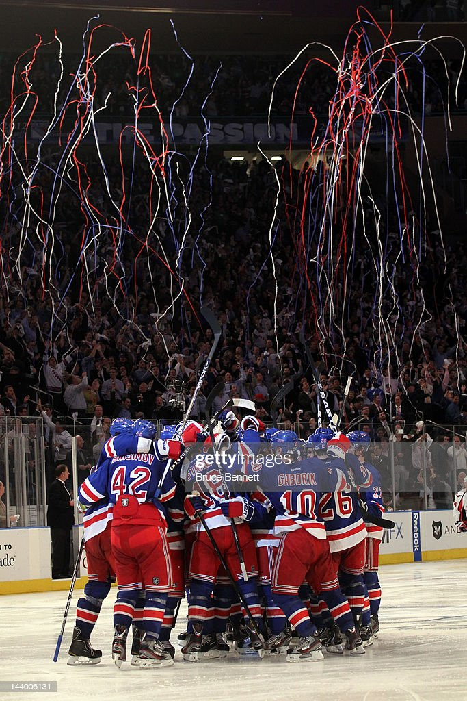 <a gi-track='captionPersonalityLinkClicked' href=/galleries/search?phrase=Marc+Staal&family=editorial&specificpeople=3809026 ng-click='$event.stopPropagation()'>Marc Staal</a> #18 of the New York Rangers celebrates with his teammates after scoring the winning goal in overtime against Braden Holtby #70 of the Washington Capitals in Game Five of the Eastern Conference Semifinals during the 2012 NHL Stanley Cup Playoffs at Madison Square Garden on May 7, 2012 in New York City. The New York Rangers defeated the Washington Capitals in overtime 2-3.