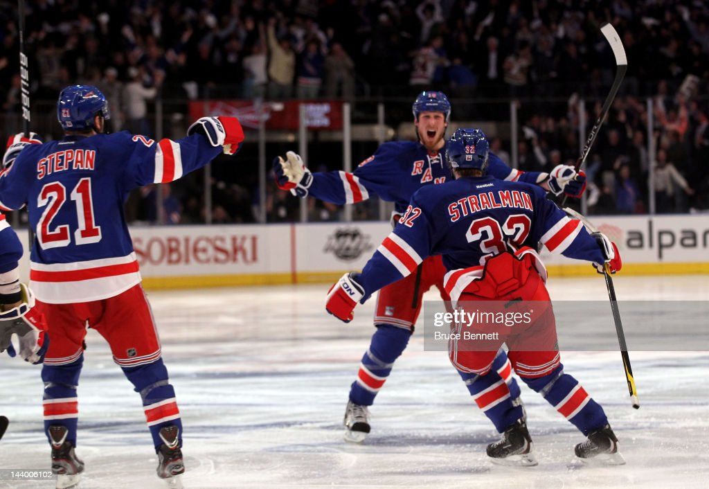<a gi-track='captionPersonalityLinkClicked' href=/galleries/search?phrase=Marc+Staal&family=editorial&specificpeople=3809026 ng-click='$event.stopPropagation()'>Marc Staal</a> #18 of the New York Rangers celebrates with teammates <a gi-track='captionPersonalityLinkClicked' href=/galleries/search?phrase=Anton+Stralman&family=editorial&specificpeople=2271901 ng-click='$event.stopPropagation()'>Anton Stralman</a> #32 and <a gi-track='captionPersonalityLinkClicked' href=/galleries/search?phrase=Derek+Stepan&family=editorial&specificpeople=4687181 ng-click='$event.stopPropagation()'>Derek Stepan</a> after scoring the winning a goal in overtime against Braden Holtby #70 of the Washington Capitals in Game Five of the Eastern Conference Semifinals during the 2012 NHL Stanley Cup Playoffs at Madison Square Garden on May 7, 2012 in New York City. The New York Rangers defeated the Washington Capitals in overtime 2-3.