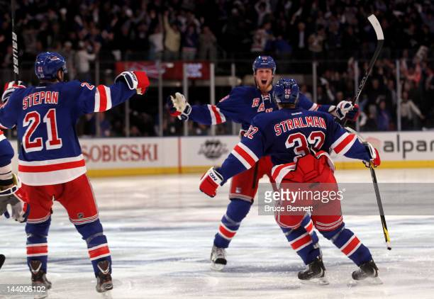 Marc Staal of the New York Rangers celebrates with teammates Anton Stralman and Derek Stepan after scoring the winning a goal in overtime against...