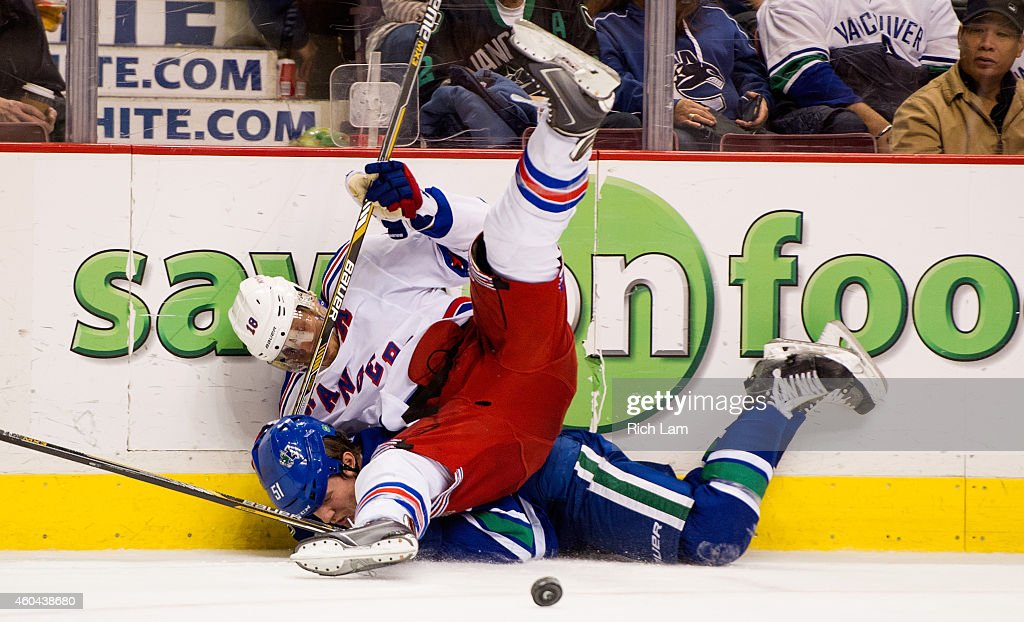 <a gi-track='captionPersonalityLinkClicked' href=/galleries/search?phrase=Marc+Staal&family=editorial&specificpeople=3809026 ng-click='$event.stopPropagation()'>Marc Staal</a> #18 of the New York Rangers falls on <a gi-track='captionPersonalityLinkClicked' href=/galleries/search?phrase=Derek+Dorsett&family=editorial&specificpeople=4306277 ng-click='$event.stopPropagation()'>Derek Dorsett</a> #51 of the Vancouver Canucks after the two collided along the side boards during the third period in NHL action on December, 13, 2014 at Rogers Arena in Vancouver, British Columbia, Canada.