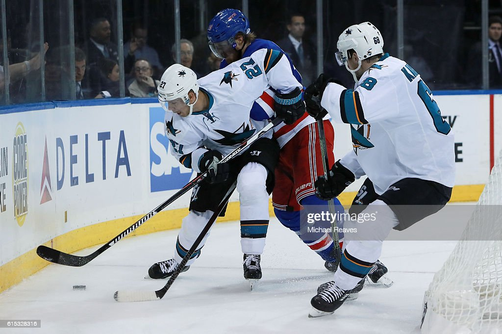 Marc Staal #18 of the New York Rangers fights for the puck with Joonas Donskoi #27 and Melker Karlsson #68 of the San Jose Sharks during the third period at Madison Square Garden on October 17, 2016 in New York City.