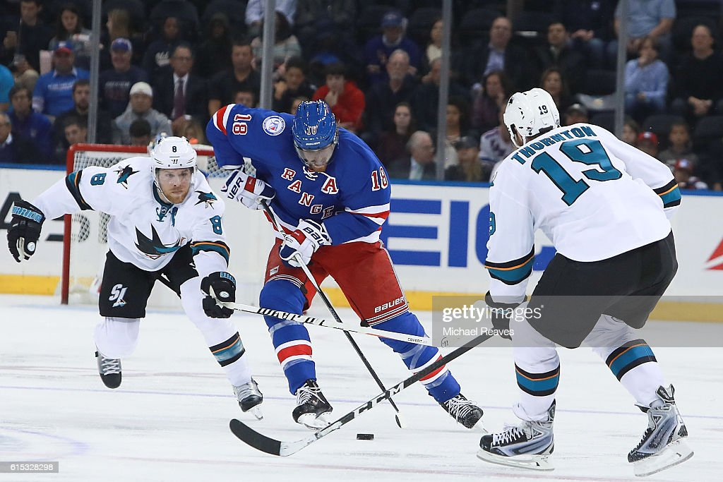 Marc Staal #18 of the New York Rangers skates through the defense of Joe Pavelski #8 and Joe Thornton #19 of the San Jose Sharks during the second period at Madison Square Garden on October 17, 2016 in New York City.