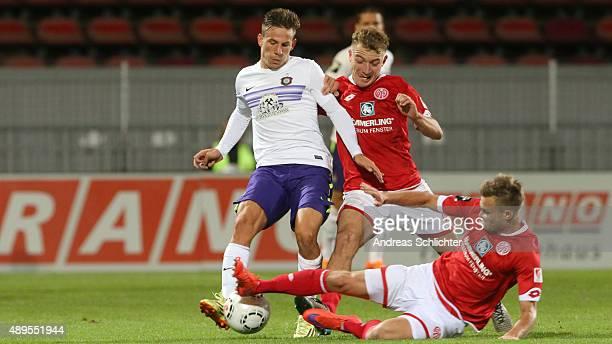 Marc Wachs and Benedikt Saller of Mainz 05 challenges Simon Skarlatidis of Erzgebirge Aue during the Third League match between 1 FSV Mainz 05 II and...