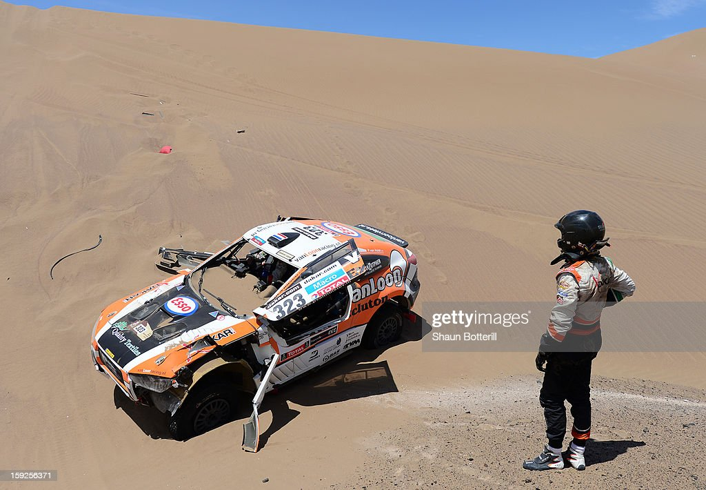 Marc Wams of team HRX waits for driver Erik Van Loon to get out of the car after crashing during in stage 6 from Arica to Calama during the 2013 Dakar Rally on January 10, 2013 in Arica, Chile.