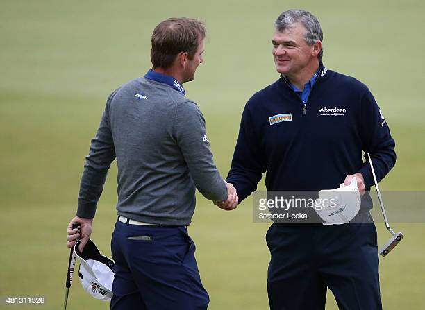Marc Warren of Scotland and Paul Lawrie of Scotland shake hands on the 18th green during the third round of the 144th Open Championship at The Old...