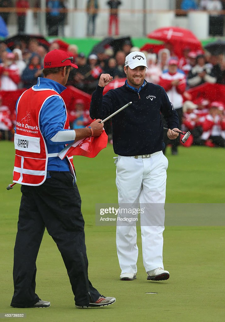 Marc Warren of Scotland celebrates on the 18th green with his caddie Ken Herring after winning Made In Denmark at Himmerland Golf & Spa Resort on August 17, 2014 in Aalborg, Denmark.