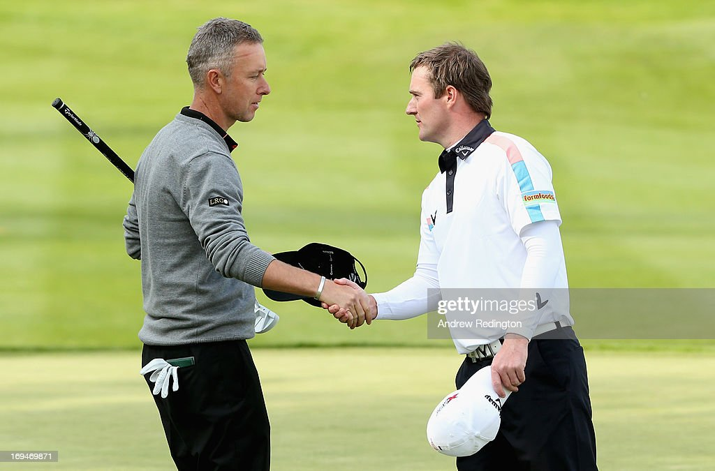 Marc Warren (R) of Scotland shakes hands with Mark Foster of England on the eighteenth hole during the third round of the BMW PGA Championship on the West Course at Wentworth on May 25, 2013 in Virginia Water, England.