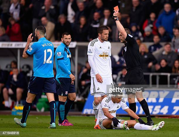 Marc Wilson of Stoke City is shown the red card by referee Craig Pawson during the Barclays Premier League match between Swansea City and Stoke City...