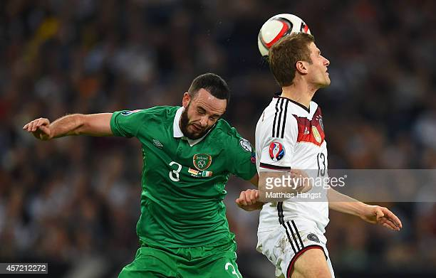 Marc Wilson of the Republic of Ireland and Thomas Mueller of Germany compete for the ball during the EURO 2016 Qualifier between Germany and Republic...