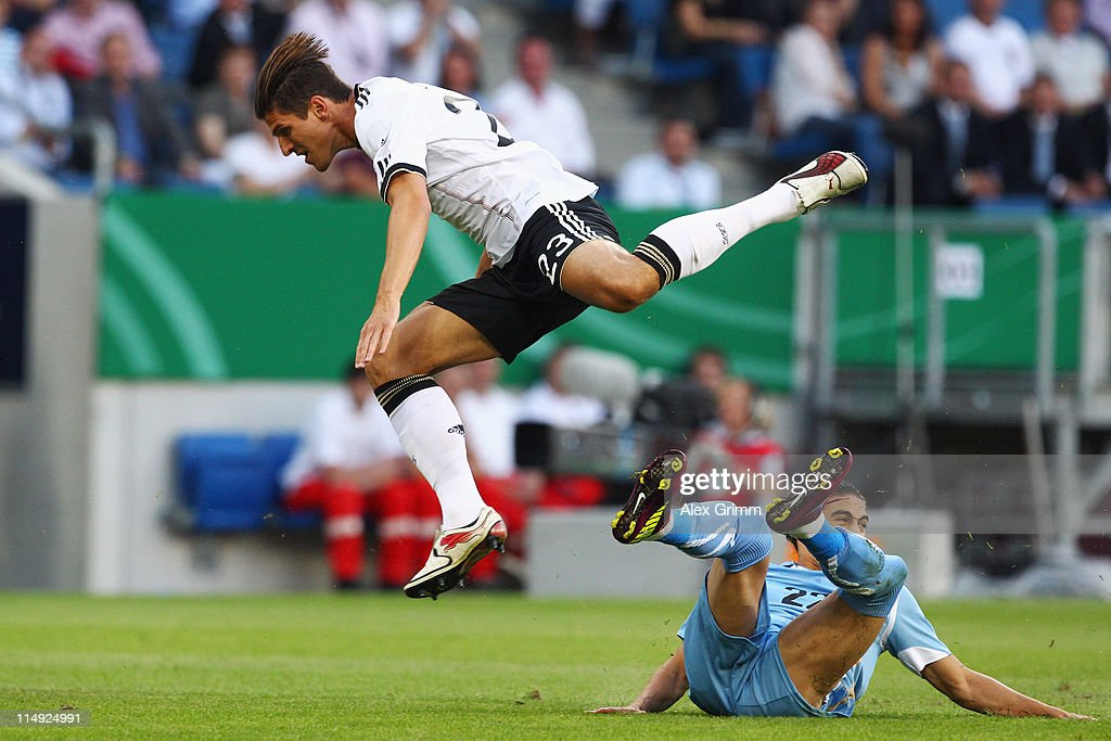Marc Ziegler (L) of Germany is challenged by Martin Caceres of Uruguay during the international friendly charity match between Germany and Uruguay at Rhein-Neckar Arena on May 29, 2011 in Sinsheim, Germany.