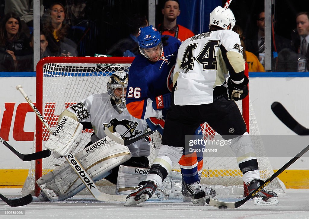 Marc-Andre Fleury #29 and Brooks Orpik #44 of the Pittsburgh Penguins defend against Matt Moulson #26 of the New York Islanders at the Nassau Veterans Memorial Coliseum on February 5, 2013 in Uniondale, New York.