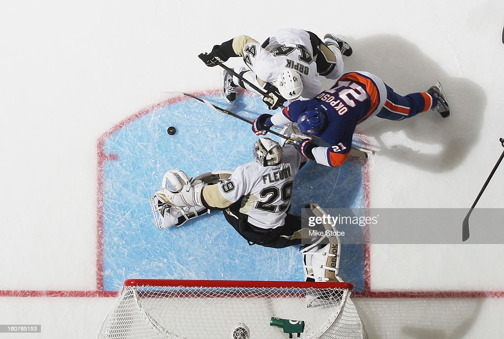 Marc-Andre Fleury #29 and Brooks Orpik #44 of the Pittsburgh Penguins defend the net against Kyle Okposo #21 of the New York Islanders at Nassau Veterans Memorial Coliseum on February 5, 2013 in Uniondale, New York. The Penguins defeated the Islanders 4-2.
