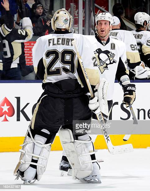 MarcAndre Fleury and Brooks Orpik of the Pittsburgh Penguins celebrate the teams win over the Toronto Maple Leafs during NHL game action March 9 2013...