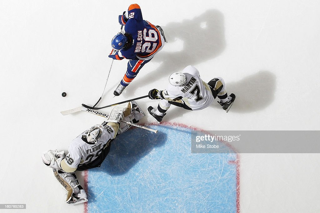 Marc-Andre Fleury #29 and Paul Martin #7 of the Pittsburgh Penguins defend the net against Matt Moulson #26 of the New York Islanders at Nassau Veterans Memorial Coliseum on February 5, 2013 in Uniondale, New York. The Penguins defeated the Islanders 4-2.
