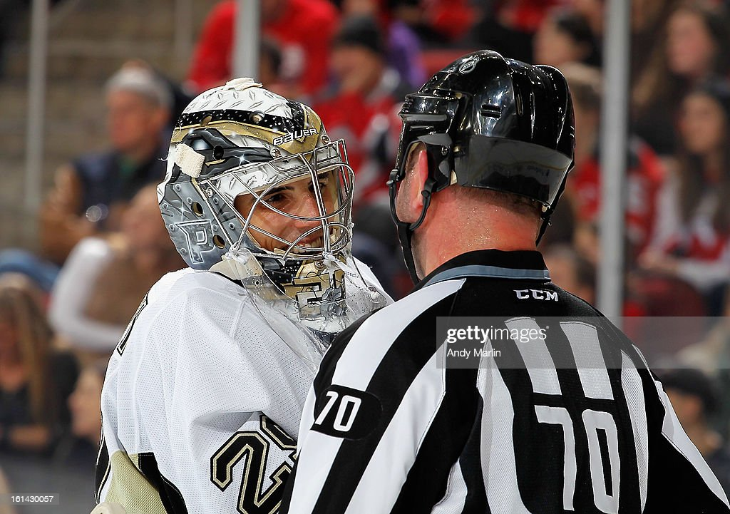 Marc-Andre Fleury #29 of the Pittsburgh Penguins and linesman Derek Nansen #70 have a chat during a timeout against the New Jersey Devils during the game at the Prudential Center on February 9, 2013 in Newark, New Jersey.