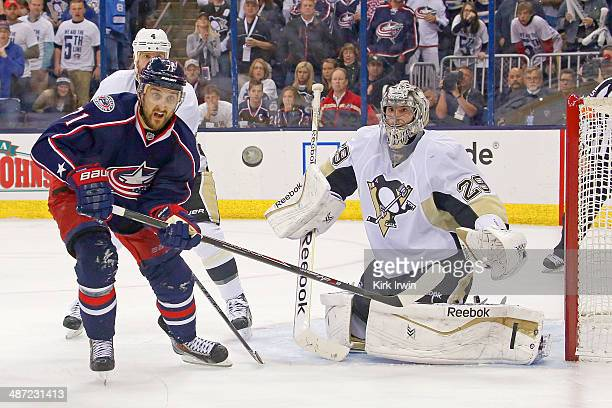 MarcAndre Fleury of the Pittsburgh Penguins deflects the puck away from Nick Foligno of the Columbus Blue Jackets during the second period of Game...