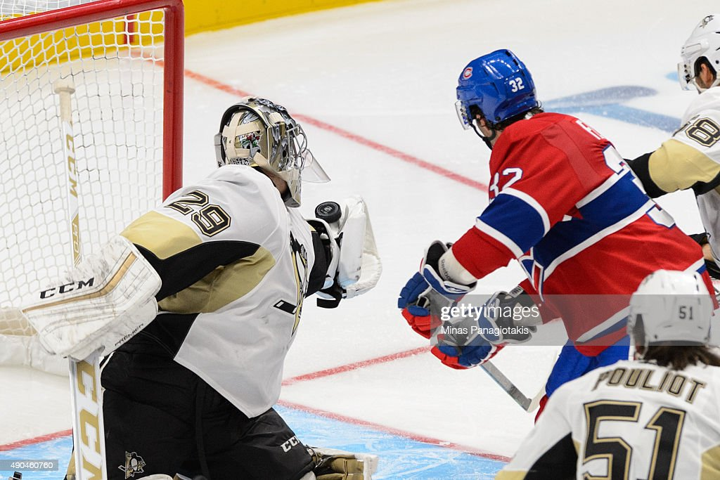 Marc-Andre Fleury #29 of the Pittsburgh Penguins gets a glove on the puck against Brian Flynn #32 of the Montreal Canadiensduring a NHL pre-season game at the Videotron Centre on September 28, 2015 in Quebec City, Quebec, Canada.