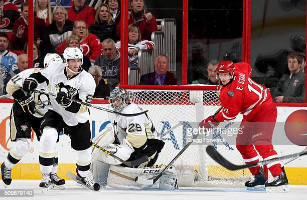 MarcAndre Fleury of the Pittsburgh Penguins goes down in the crease to protect the goal as teammate Brian Domoulin defends and Eric Staal of the...